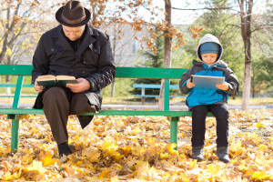 Elderly man and small boy sharing a park bench